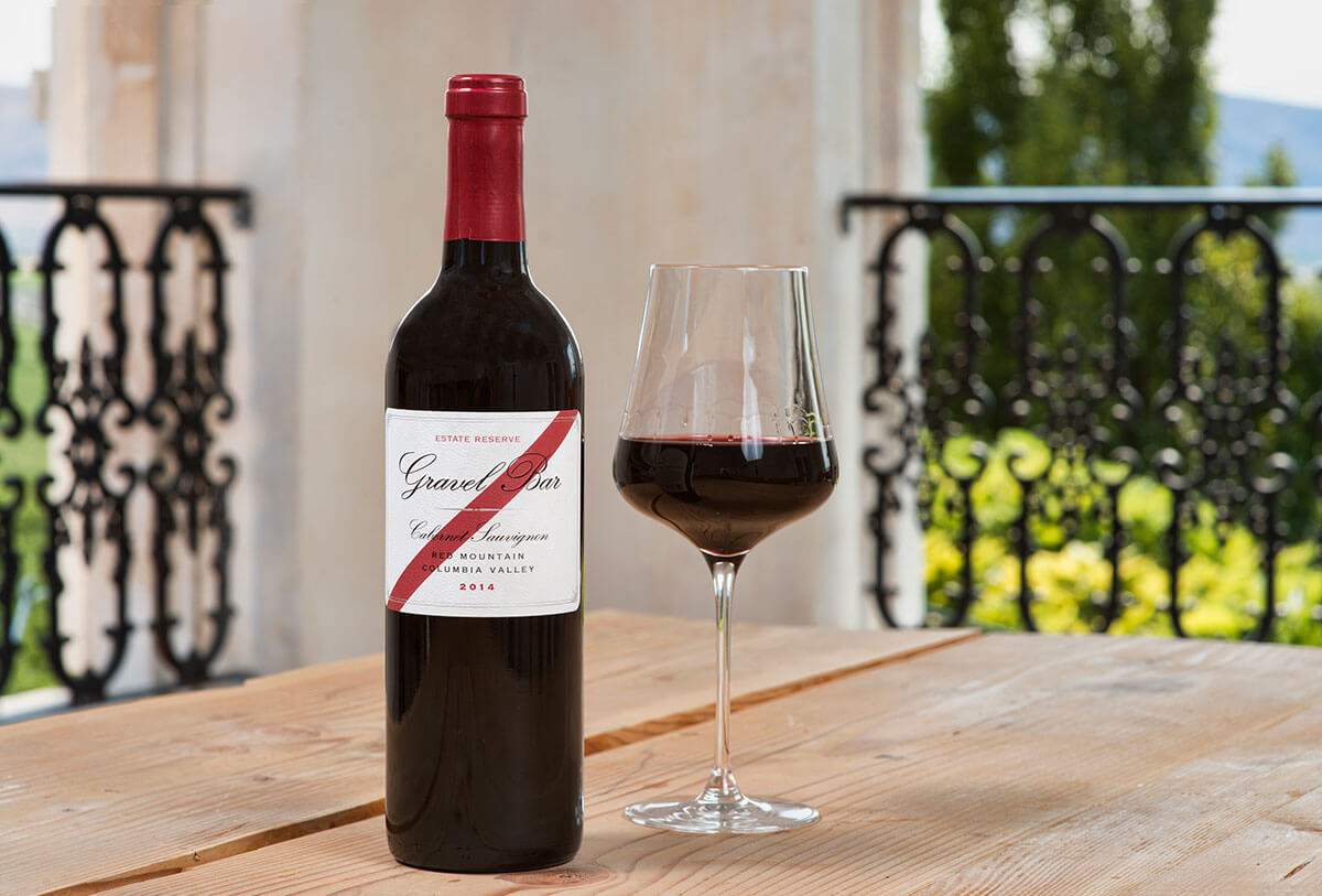 A bottle of Cabernet Sauvignon Reserve sits on a wooden table accompanied by a glass of wine